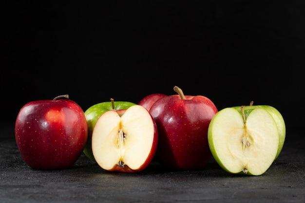 다채로운 사과 신선한 잘 익은 부드러운 육즙 반 잘라 어두운 책상에 고립