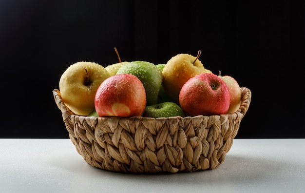 Colorful apples in a wicker basket on black and white