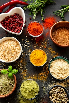 Colorful and aromatic herbs and spices on a dark table