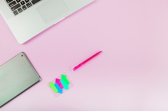 Colorful arrow symbols; digital tablet; laptop and pen on pink background