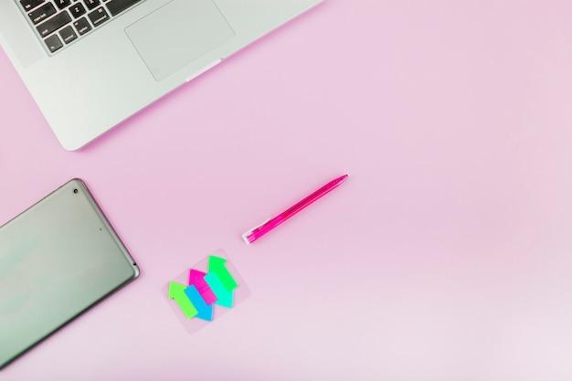 カラフルな矢印記号;デジタルタブレット;ノートパソコン、ペン、ピンク、背景