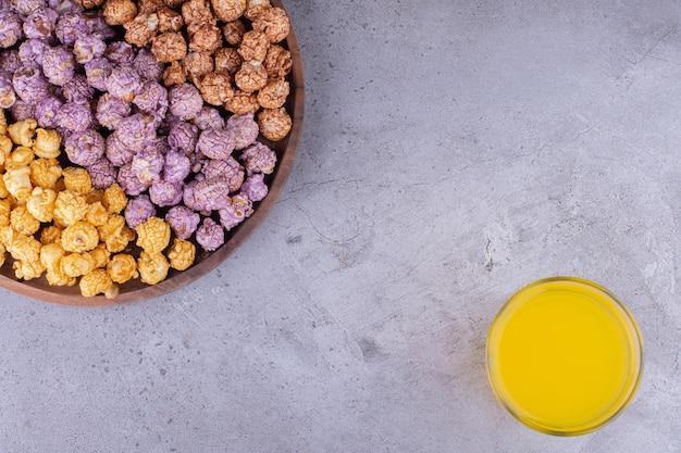 대리석 배경에 탄산 음료 한 잔과 함께 나무 쟁반에 다채로운 모듬 팝콘 사탕. 고품질 사진
