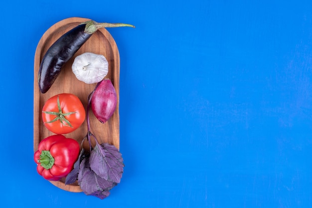 Colorful assortment of fresh ripe vegetables on wooden board.
