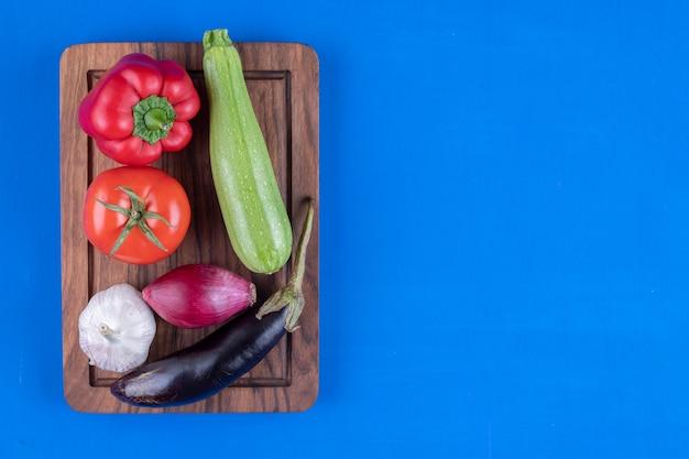 Assortimento variopinto di verdure fresche mature su tavola di legno.