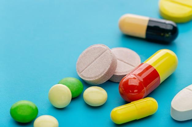 Красочный ассортимент таблеток и капсул на синем фоне, крупным планом.
