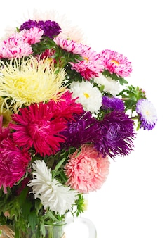 Colorful  aster flowers bouquet in glass  vase close up isolated on white background