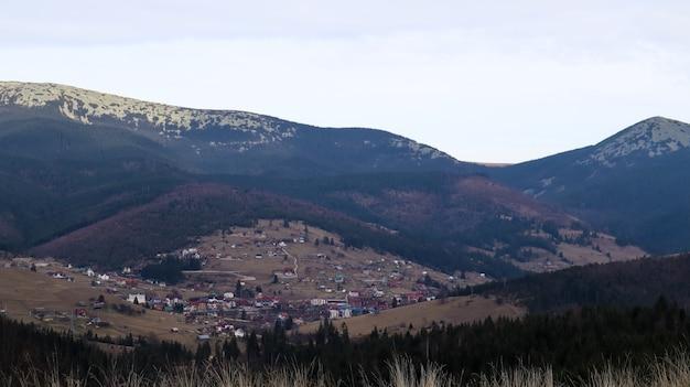 Красочный осенний пейзаж в горной деревне. туманное утро в карпатах. украина, европа. красивые холмы и дома. мир красоты. вид на горы осенью. красивый природный ландшафт.