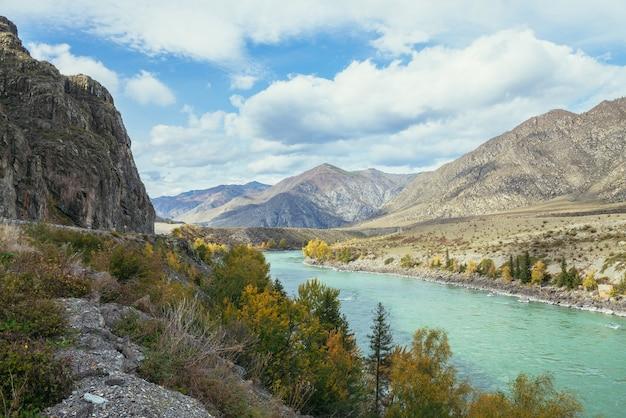 日差しの中で広いターコイズブルーの山川沿いの木々に黄金の葉を持つカラフルな秋の風景。大きな山川と秋の金色の黄色い木々のある明るい高山の風景