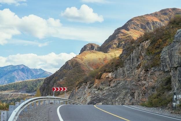 日差しの中で岩に沿って山の高速道路とカラフルな秋の風景。秋の色の山道と明るい高山の風景。秋の時間の山の高速道路。美しい岩壁に沿った道。