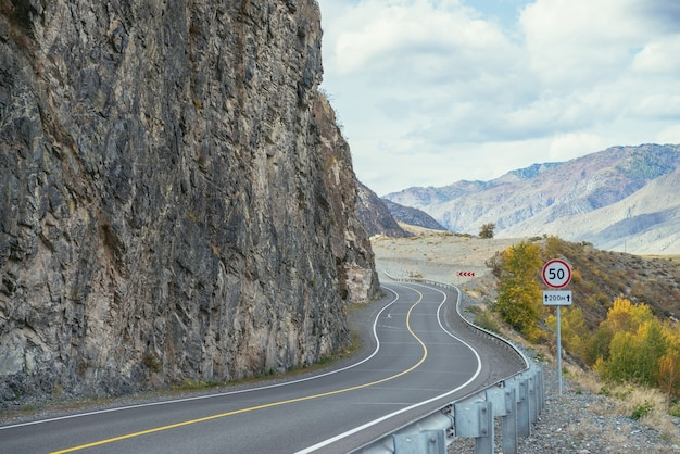 日差しの中で岩に沿って山の高速道路とカラフルな秋の風景。秋の色の山道と明るい高山の風景。秋の山の高速道路。美しい岩壁に沿った道。
