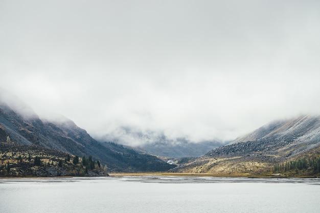 低い雲の針葉樹と岩や丘に囲まれた山の湖とカラフルな秋の風景。低い雲の中に湖と高いロッキー山脈と黄金の秋の色の美しい高原の風景
