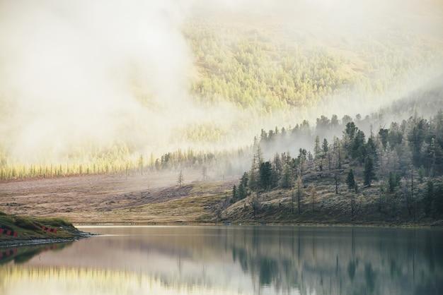 山の湖と針葉樹のあるカラフルな秋の風景。丘の上に霜が降り、低い雲の中で黄金色の太陽の下で森の山を眺めることができます。霧の中で太陽に照らされた黄色と冷ややかな白いカラマツ。