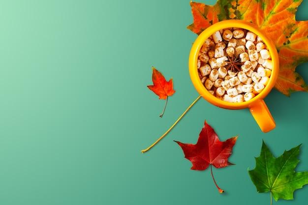 Разноцветные осенние листья с горячим напитком на глубокой мятой