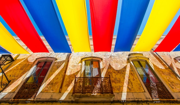 Colorful awning on the street in summer. outdoor view of the typical architecture of the city of loule, portugal.