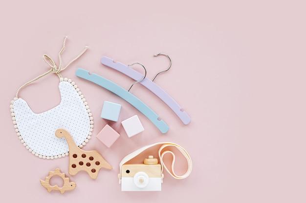 다채로운 아기 옷걸이, 나무 장난감과 치발기가 있는 턱받이. 파스텔 핑크색 배경에 신생아를 위한 아기 용품과 액세서리 세트. 베이비 샤워 개념입니다. 평평한 평지, 평면도