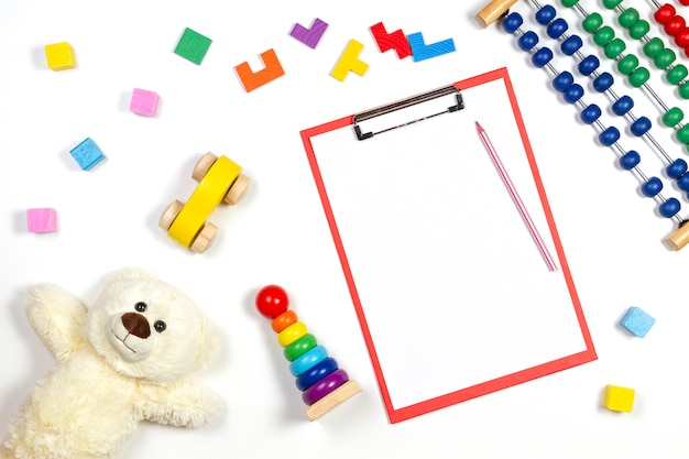 Colorful baby kid toys and red clipboard with blank sheet of paper. top view