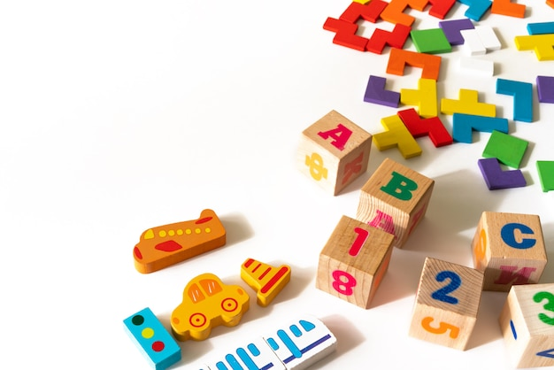 Colorful baby kids toys on white background. frame from developing colorful blocks, cars and airplane, puzzles. top view. flat lay. copy space for text