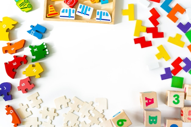 Colorful baby toys on white background. frame from developing wooden blocks, cars and puzzles. natural, eco-friendly toys for children. top view. flat lay. copy space.
