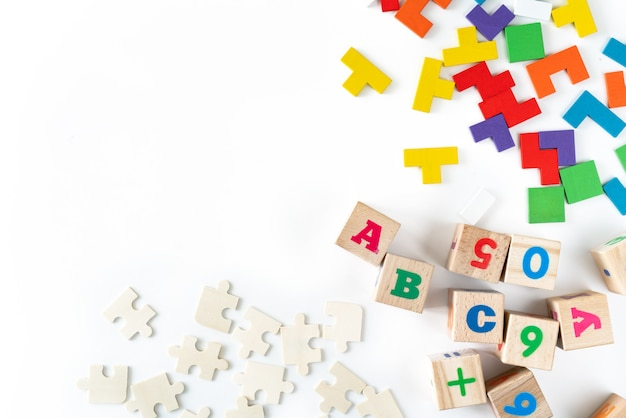 Colorful baby toys on white background. frame from developing wooden blocks, cars and puzzles.