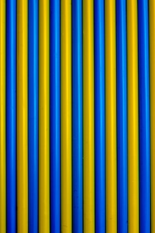 Colorful background. multicolored plastic drinking cocktail straws. blue and yellow backgr