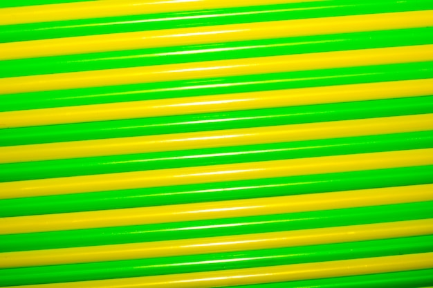 Colorful background. multicolored plastic drinking cocktail straws. green and yellow backg