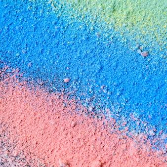 Красочная предпосылка порошка мела. разноцветные частицы пыли, разбрызганные на черном фоне.