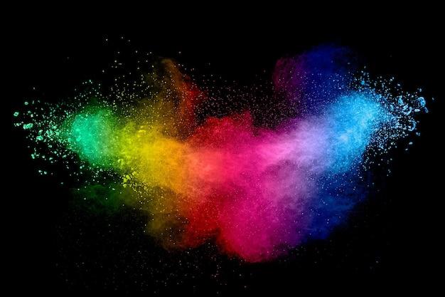 パステルパウダー爆発のカラフルな背景。黒い背景に虹色のほこりのしぶき。