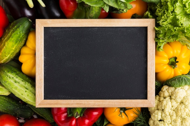 Colorful background with vegetables and blackboard