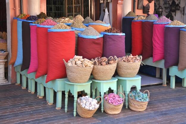 マラケシュの小さな店にあるハーブとスパイスのカラフルなバッグ、モロッコの化粧品のバスケットと石鹸