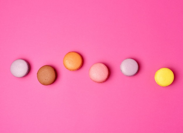 Colorful baked macarons almond flour on a pink background