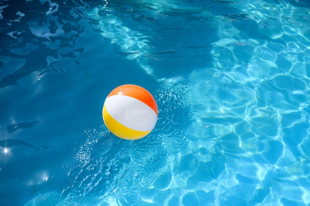 プールの青い水にカラフルなボール、誰もいません。晴れた日、夏休み、アクティブなライフ スタイルのプールサイドでのスポーツとエンターテイメント