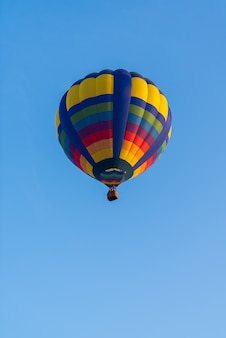 Colorful of balloon on blue sky with copy space, vertical