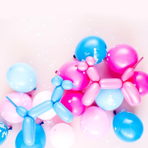 파스텔 핑크 배경에 다채로운 풍선과 풍선 개. 축제 또는 생일 파티 개념입니다. 평평한 평지, 평면도.