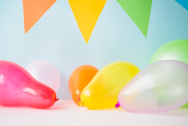 Colorful balloons and bunting against blue background