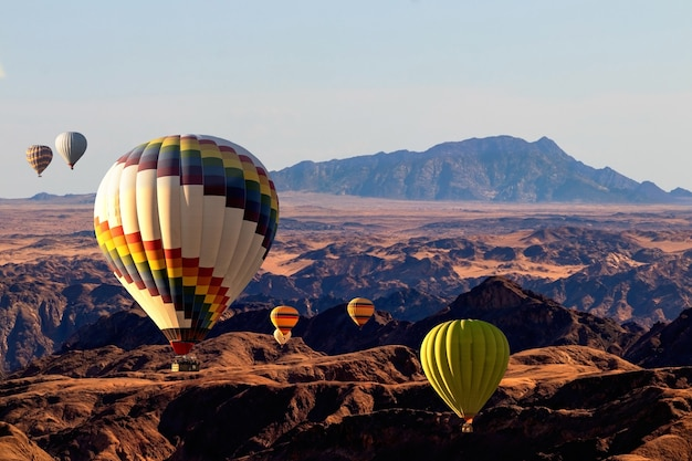 Colorful balloons flying over the moon valley mountain. africa. namibia.