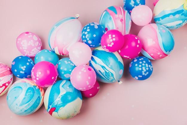 Красочные воздушные шары на фоне пастельных тонов. концепция праздничного или дня рождения. плоская планировка, вид сверху.