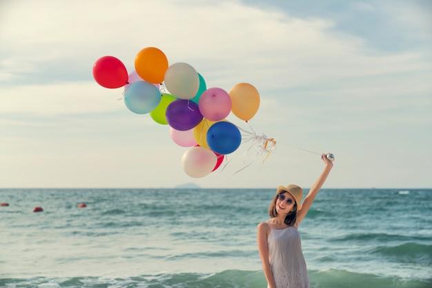 해변에서 다채로운 풍선입니다. 푸른 바다 바닥과 하늘과 재미있는 여자의 초상화