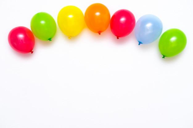 白い壁またはテーブルトップビューにカラフルな風船。お祝いやパーティーの背景。フラットレイアウトスタイル。テキストのコピースペース。誕生日グリーティングカード。