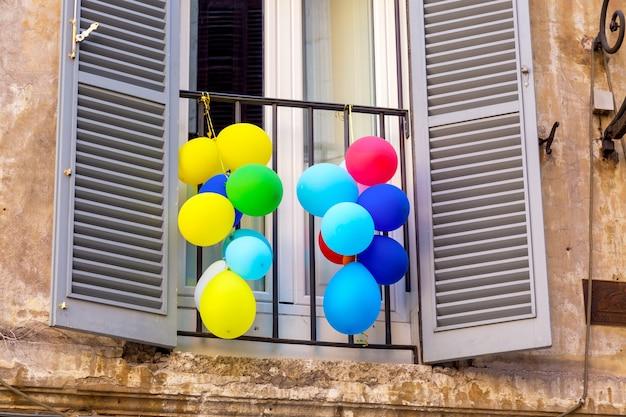 イタリア、ローマの窓にカラフルな風船。