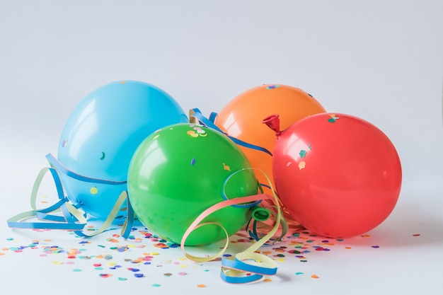 Colorful balloons on the paper confettis on a white surface