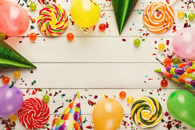 Colorful balloons on white rustic wood birthday background top view