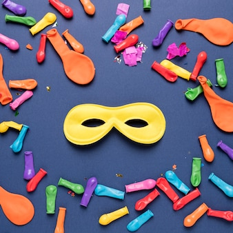 Colorful balloons with colorful confetti and yellow carnival mask