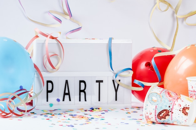 Colorful balloons with paper confettis and a led lamp board with [party] written on it