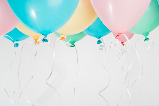 Colorful balloons with ribbons on gray background