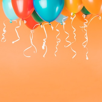 Colorful balloons with ribbons on orange background with copy space