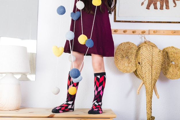 Colorful balls and hearts hanging on string in front of girl standing over tabletop