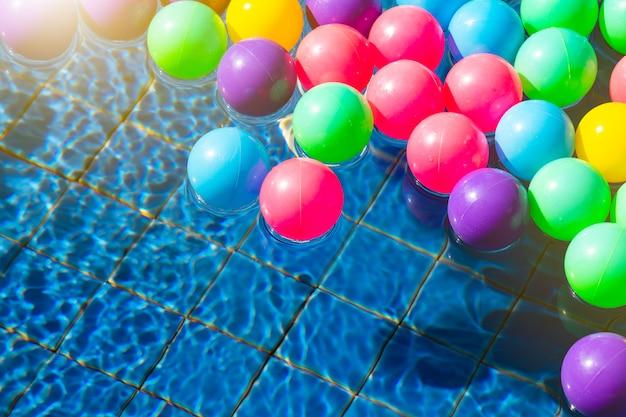 Красочные шары в бассейне по утрам с копией пространства, лето, отдых и расслабляющая концепция
