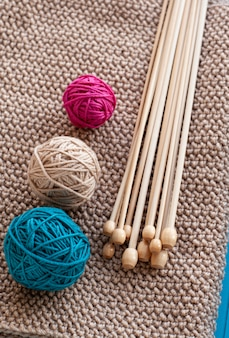 Colorful balls and wooden needles lying on beige knitted blanket