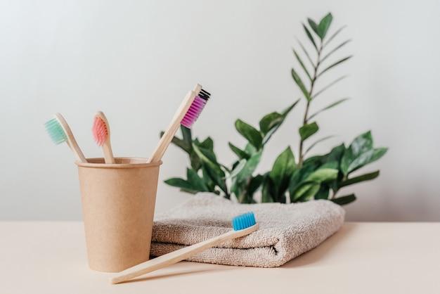 タオルと緑の植物と紙コップのカラフルな竹の歯ブラシ、ゼロウェイストコンセプトの歯科治療、持続可能なライフスタイル