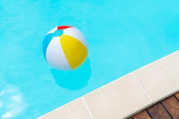 Красочный пляжный мяч, плавающий в бассейне.